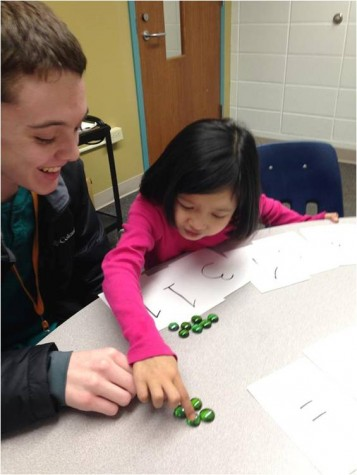 Jacob Kelleher, Junior, helps child, Say Ray, with some work.