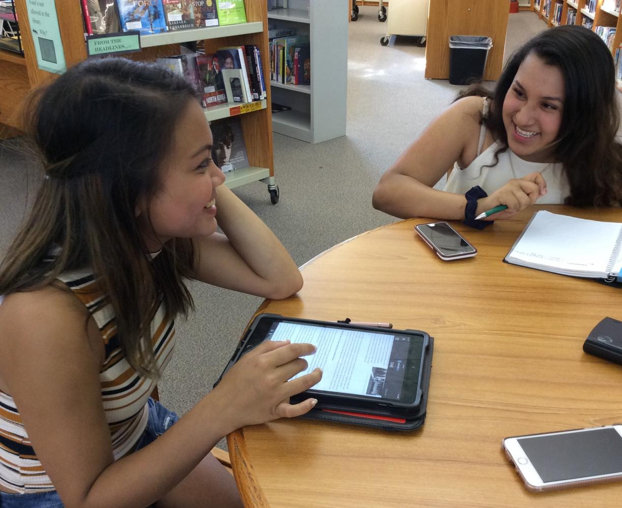 Two friends enjoy hanging out in the library.