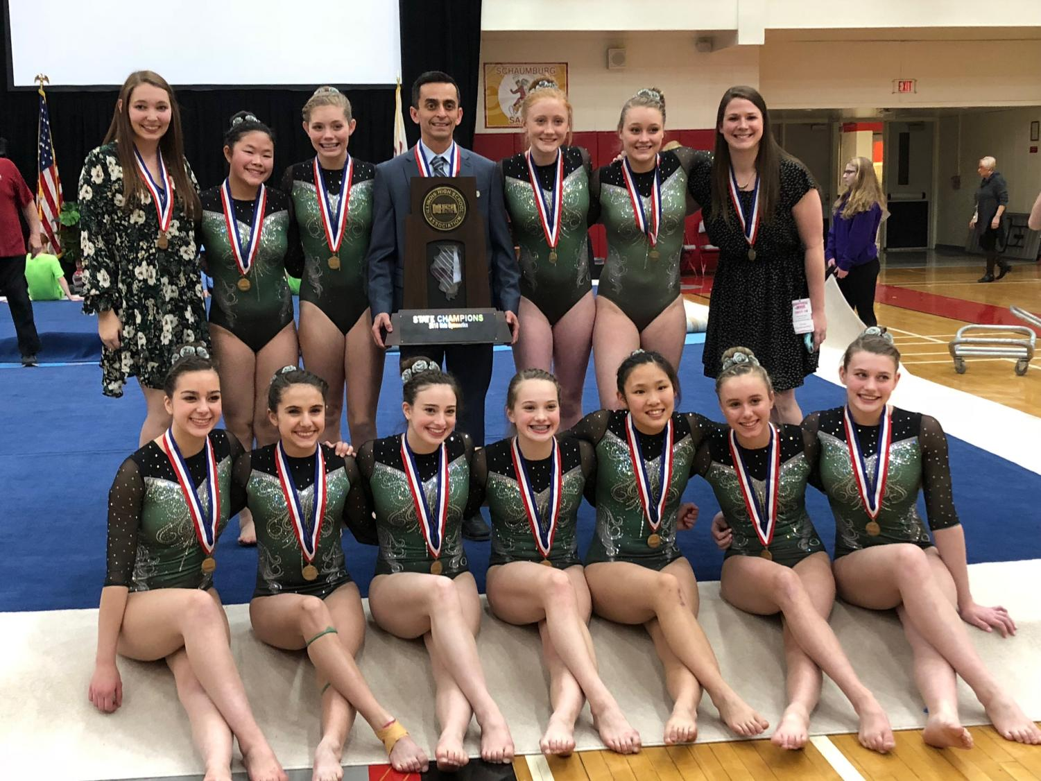 The 2017-2018 Girls' Gymnastics team holds their HUGE trophy!