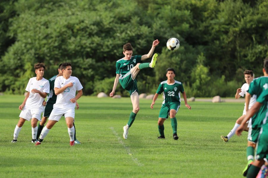 A ball is cleared from the goal box by Luke Frigo (junior).