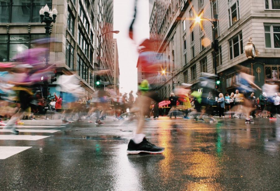 A myriad of runners pass by as long exposure elongates their strides.