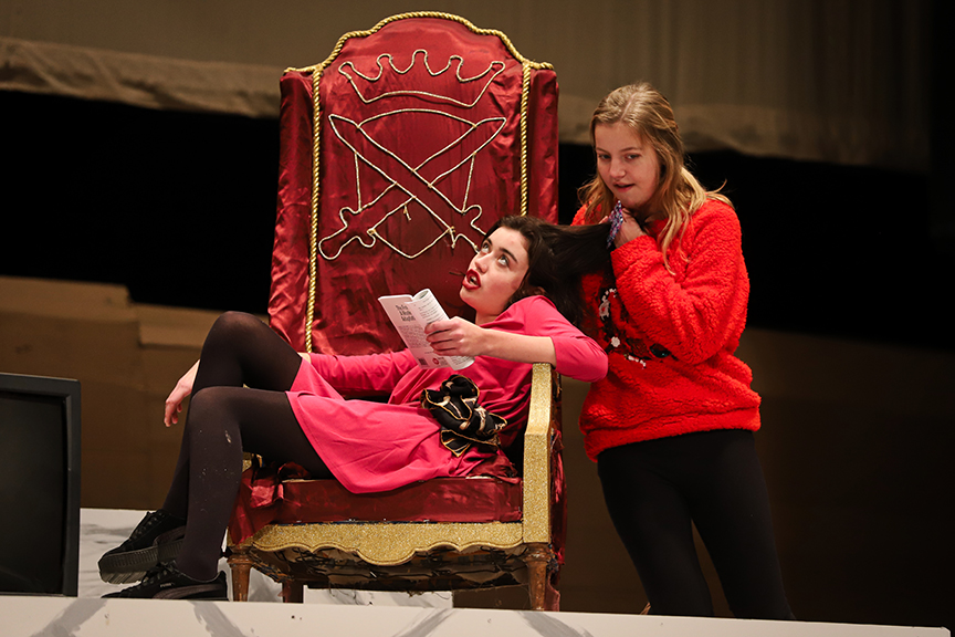Queen Persephone is attended to by her attentive hair-brushing servant (Grace Metcalf).
