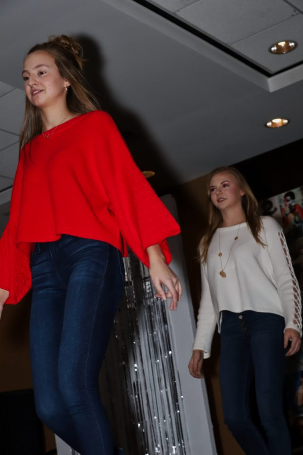 Emma Ohrenstein (junior, red sweater) and Sydney Melms (sophomore, white sweater) strut down the runway.