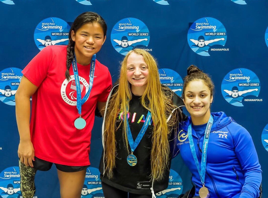 Ahalya shows off her medal with two of her teammates on the the U.S. Paralympic Swimming National Team.