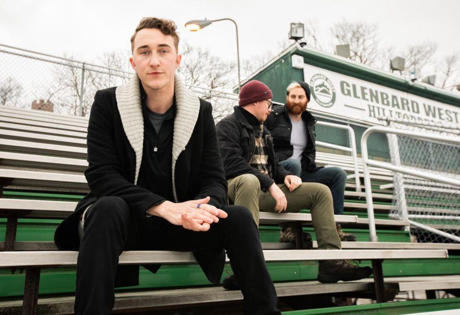 Jeff Pridgen, lead vocalist of Poe the Passenger and Class of 2011 GBW Alumni, sits on the bleachers at Duchon while band members, Matt Rosenblum, center, and Trent Maderosian, farthest right. Pridgen discussed his role in the formation, inspiration, and development stages of the trio's emerging alt-rock band.