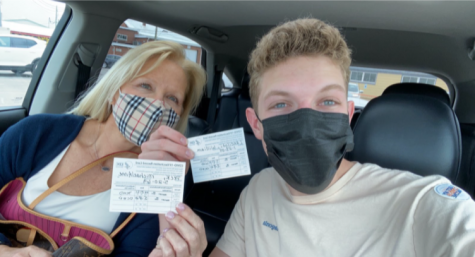 Editor and Writer, Will Lanciloti, holding up his vaccination card along with his mom.
